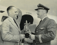 Paul E. Richter Jr., Executive Vice President of T.W.A., presents Tommy Tomlinson with a trophy